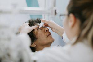 Especialista oftalmólogo aplicando gotas a paciente por ojo seco